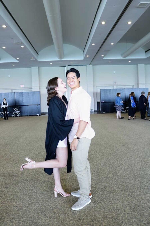 Woman in graduation robe holding boyfriend
