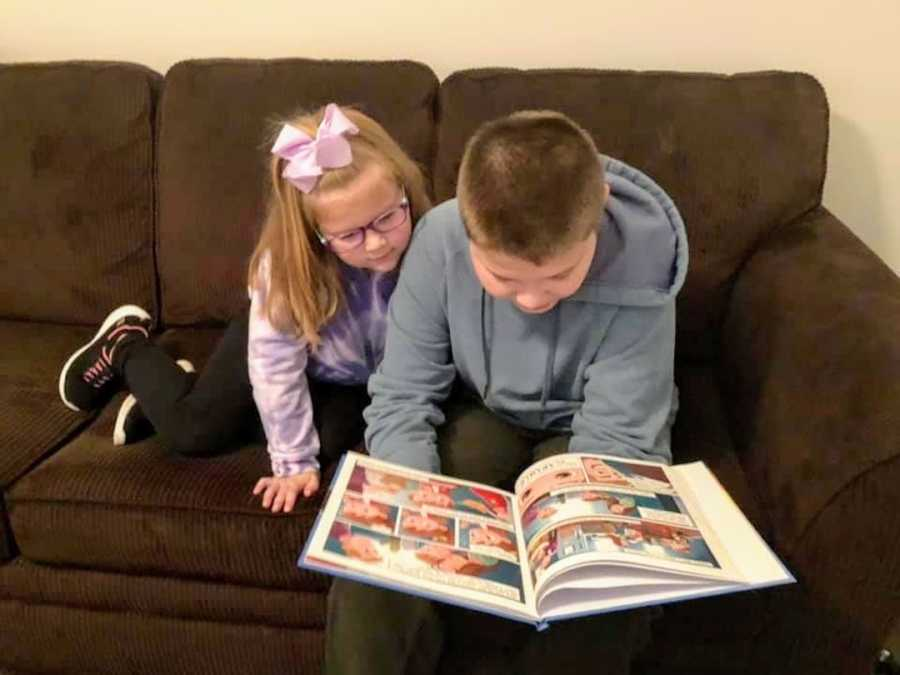 Sister and brother sitting on brown couch reading a children's book