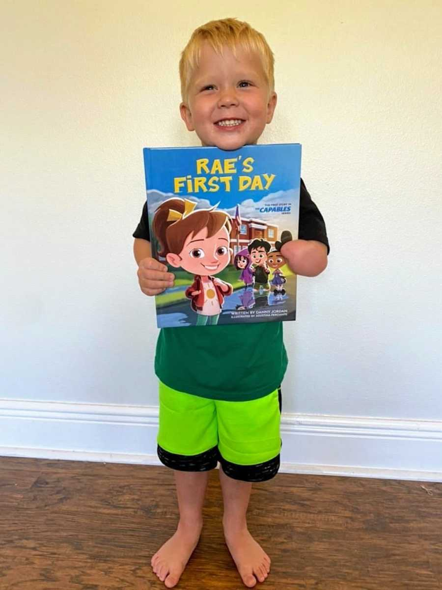 Young blonde boy with limb difference holding children's book