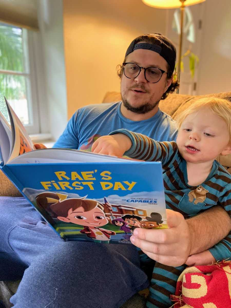 Father and son sitting on a couch reading a children's book