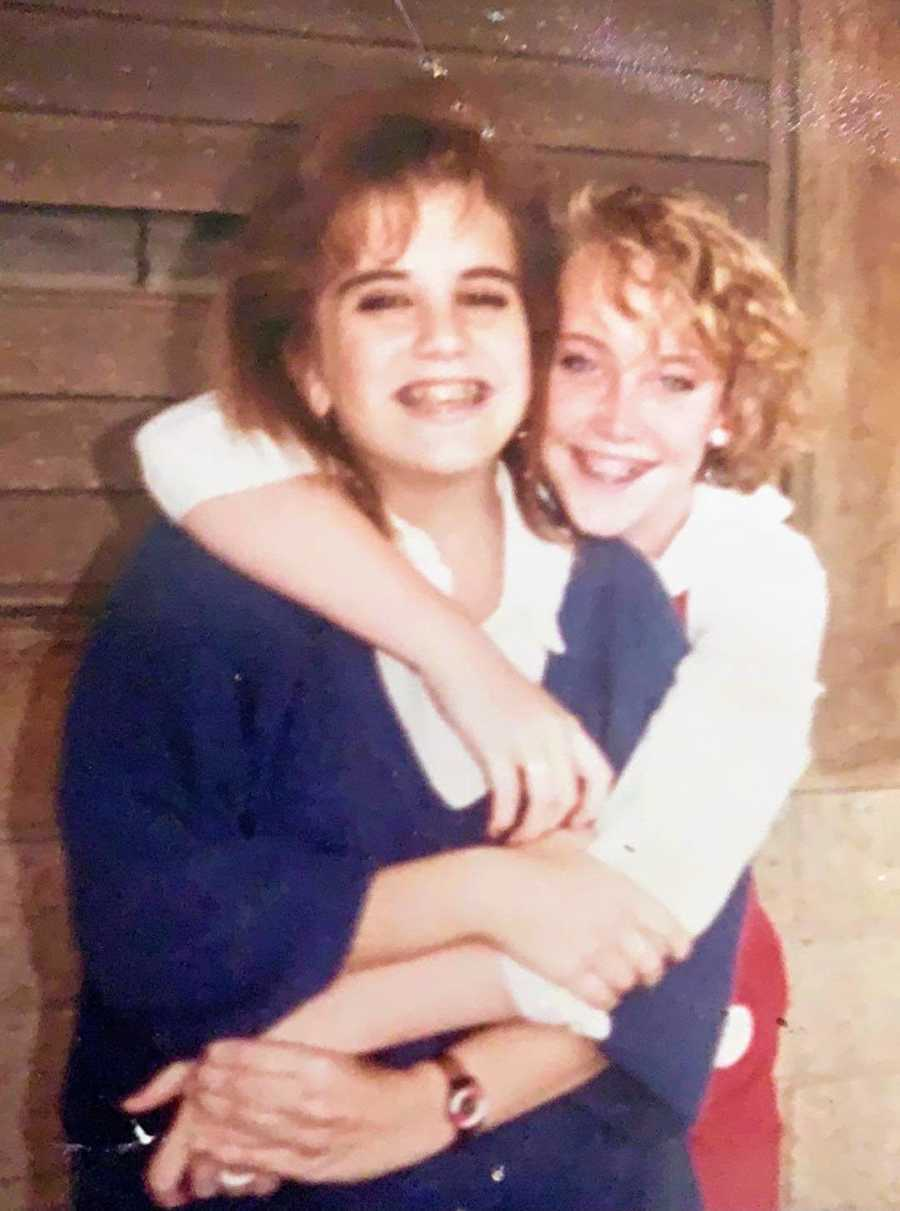A young woman wraps her arms around a friend