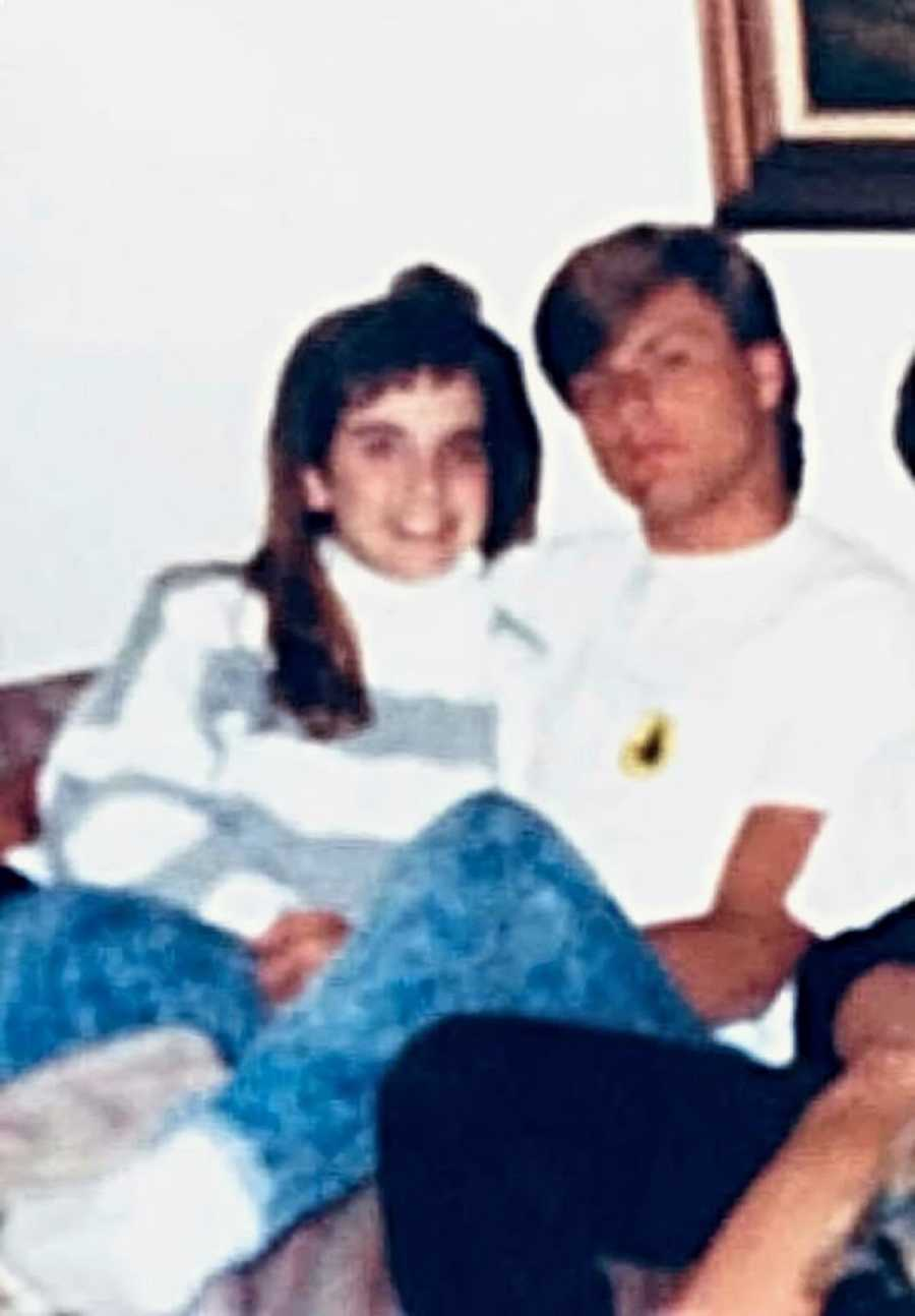 A young woman and a young man sit together on a sofa