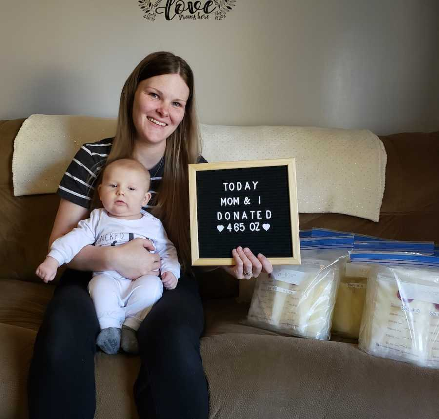 woman with baby holding sign 'donated breastmilk'