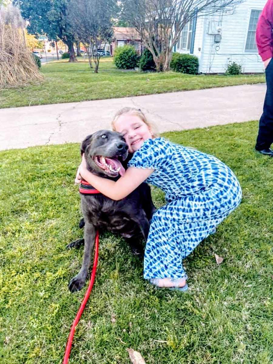 girl in blue dress hugs drooling pitbull