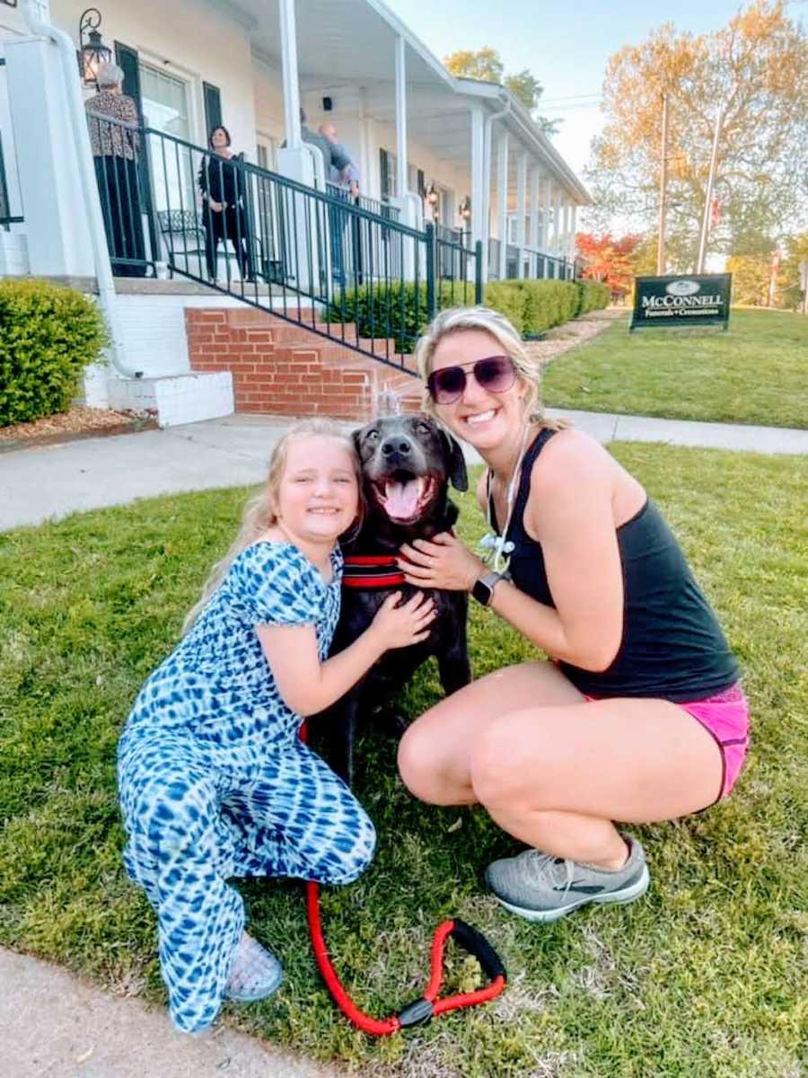stranger in sunglasses and girl in blue dress hug pitbull outside funeral home