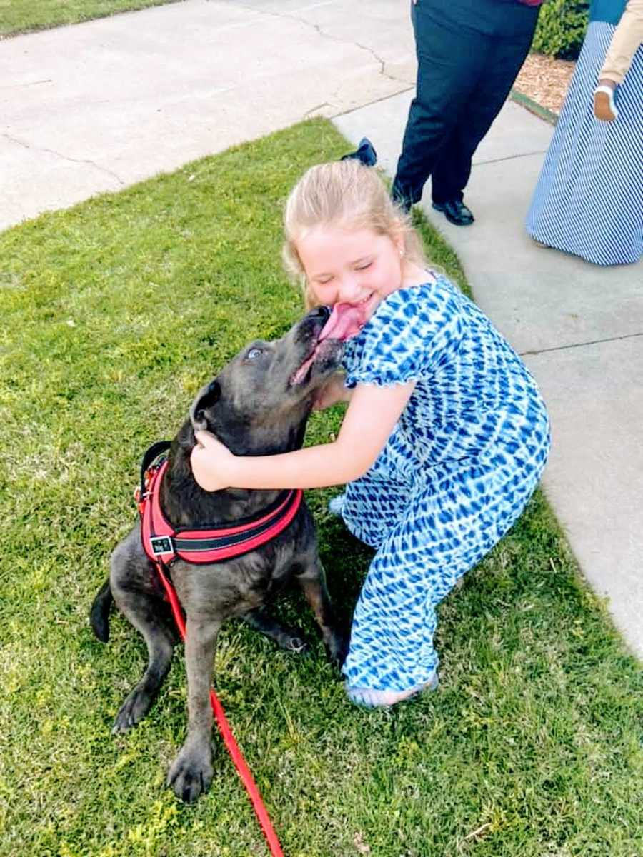 girl in blue dress smiles with pitbull