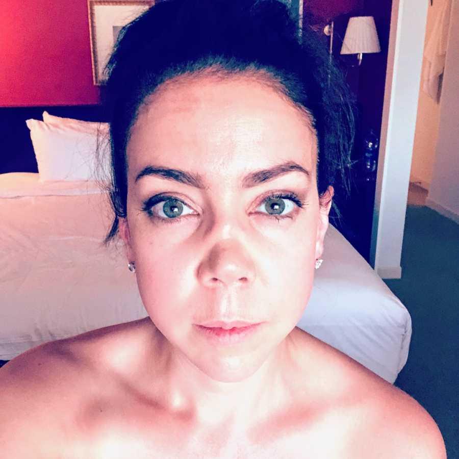 Woman with dark hair taking selfie in bedroom