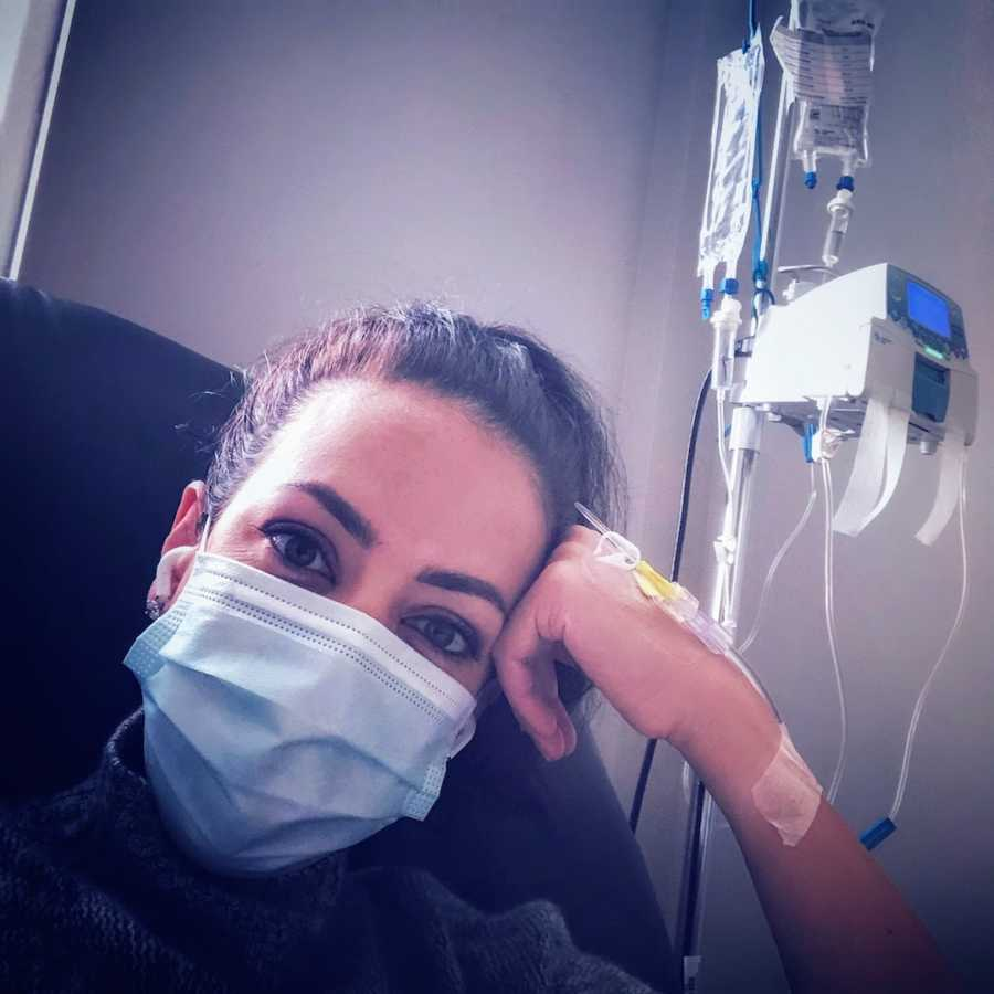 Woman wearing ponytail and facemask getting treatment by IV in hospital