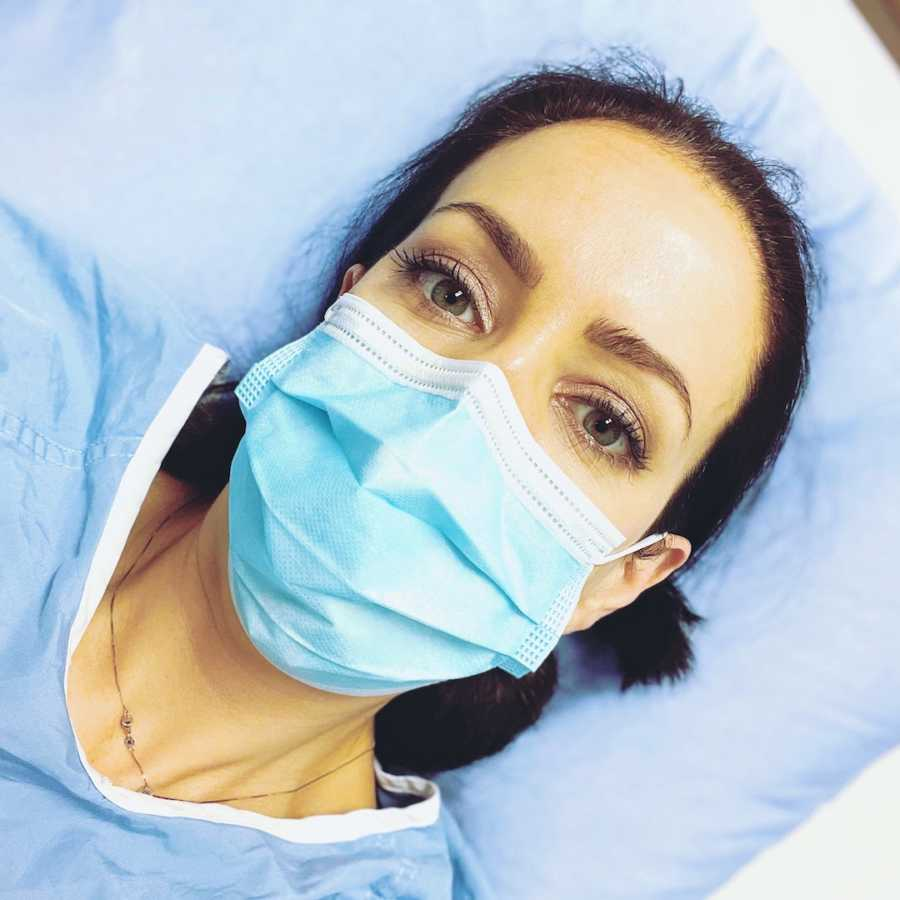 Woman lying down in hospital bed wearing hospital gown and face mask
