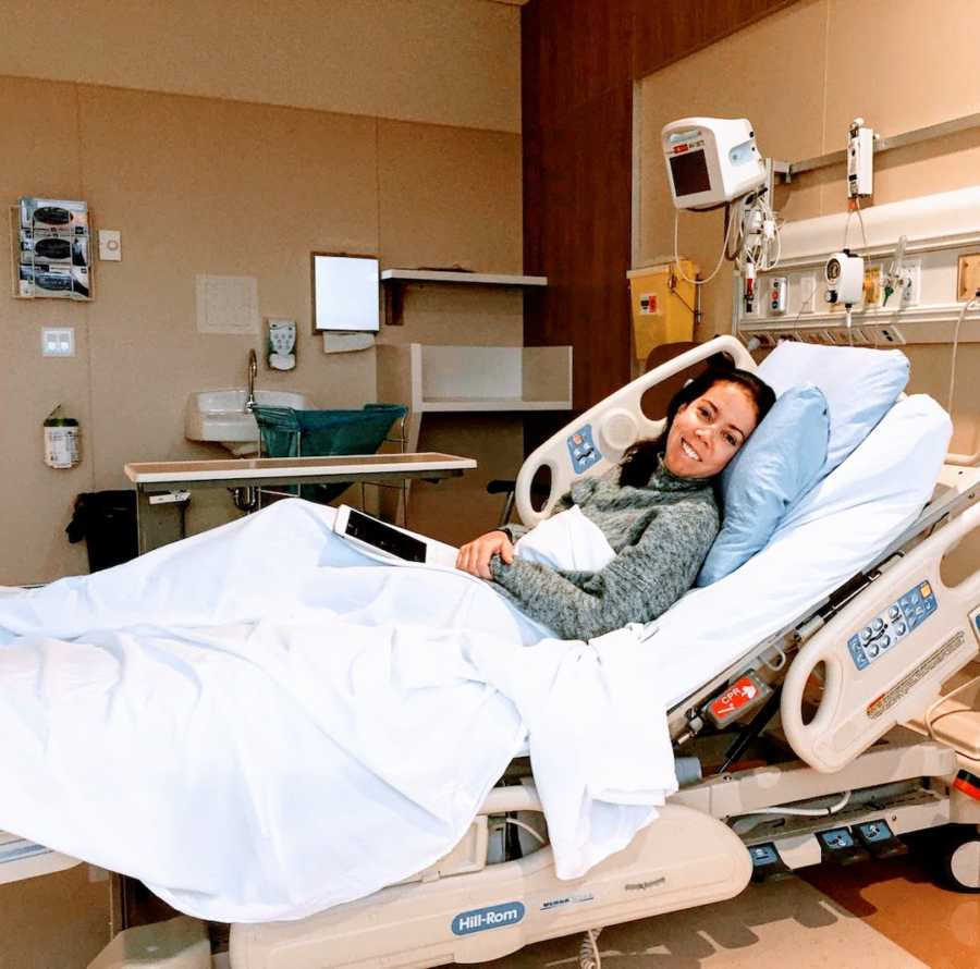 Woman smiling and lying in hospital bed with blue sheets