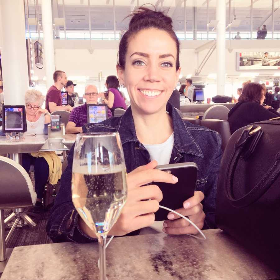 Woman smiling and holding phone in restaurant with glass of champagne