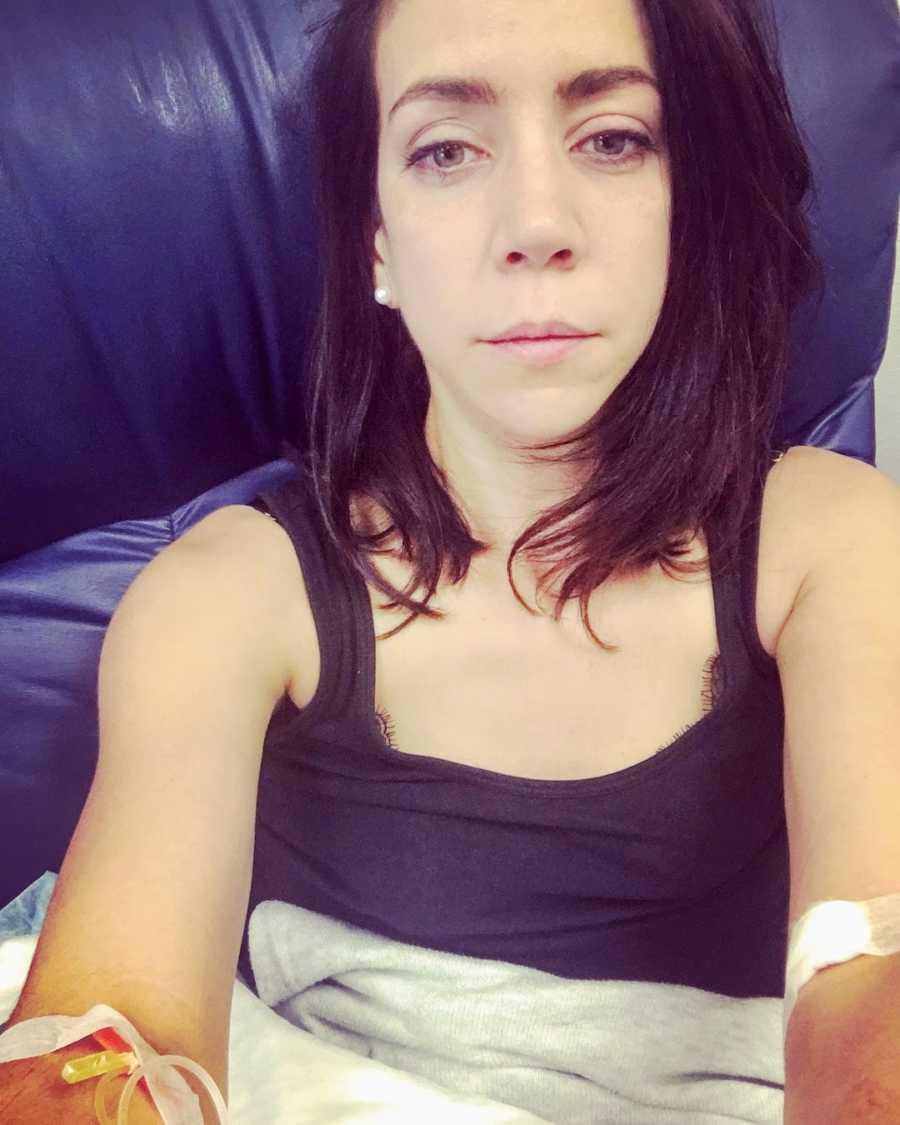 Woman with IVs wearing black tank top taking selfie