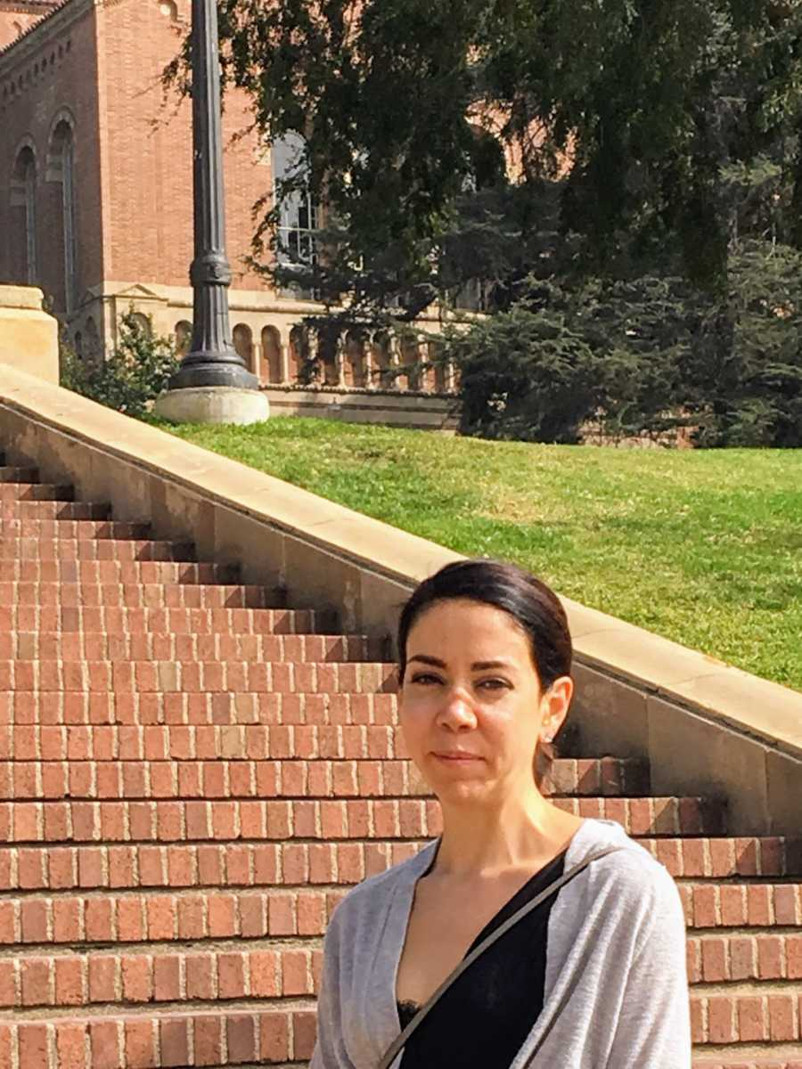 Woman smiling standing in front of red brick steps