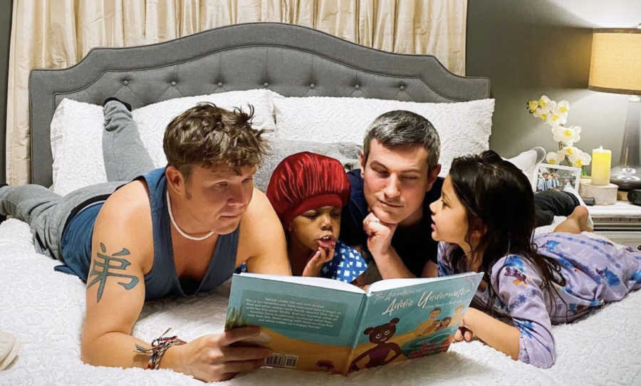Two gay dads reading a book to their adopted daughters