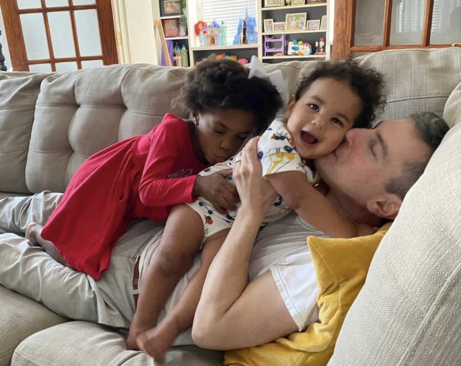 Gay dad kissing his adopted daughter