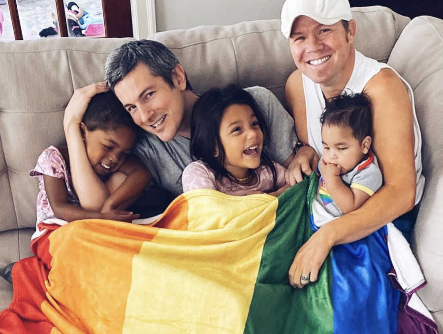 Two gay dads holding their three mixed race, adopted children and a rainbow flag