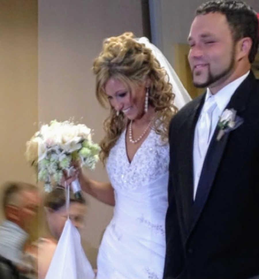 Newlywed husband and wife walking down the aisle at wedding