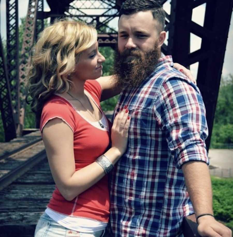 Couple posing standing on bridge outside