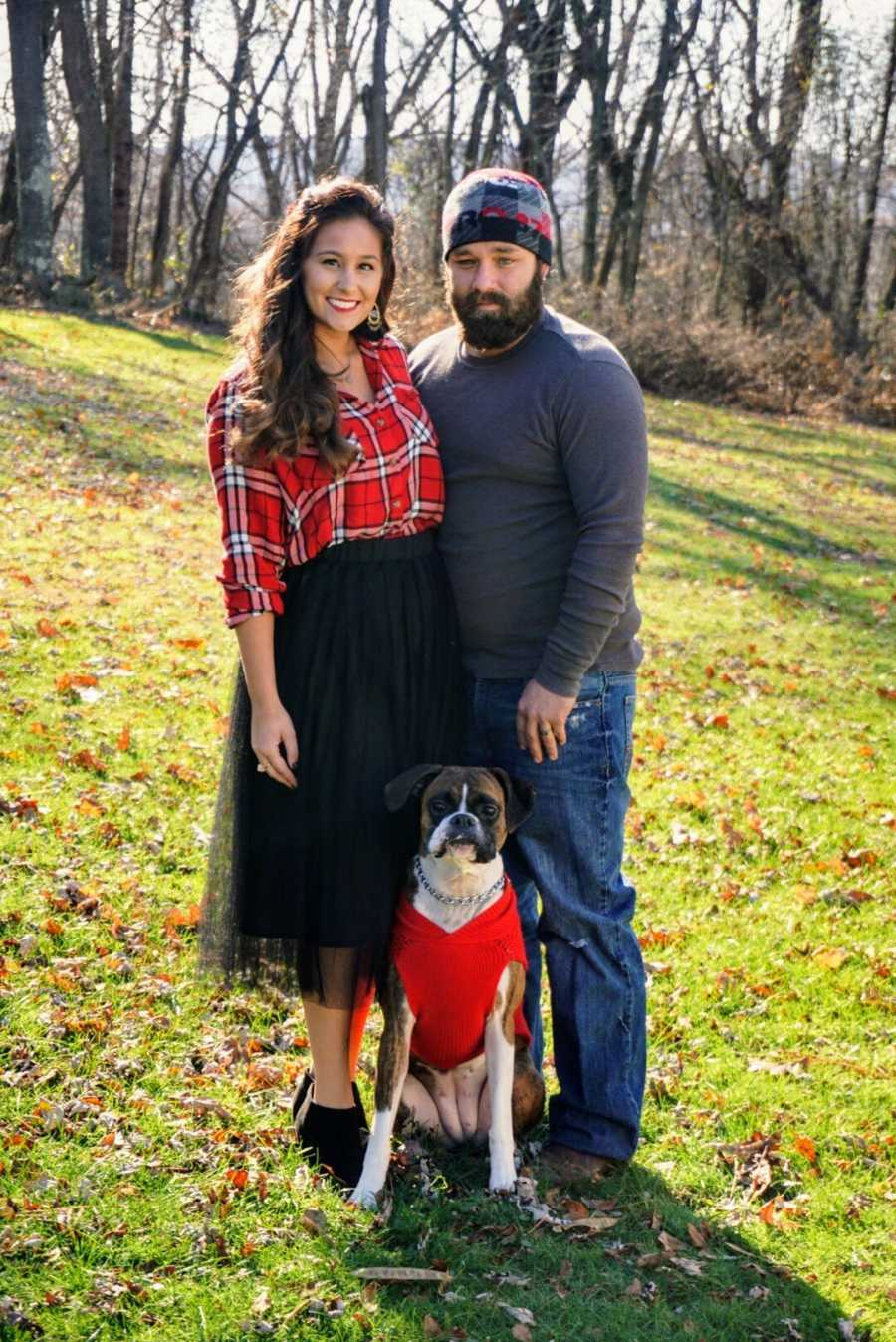Husband and wife smiling and standing outside with Boxer dog