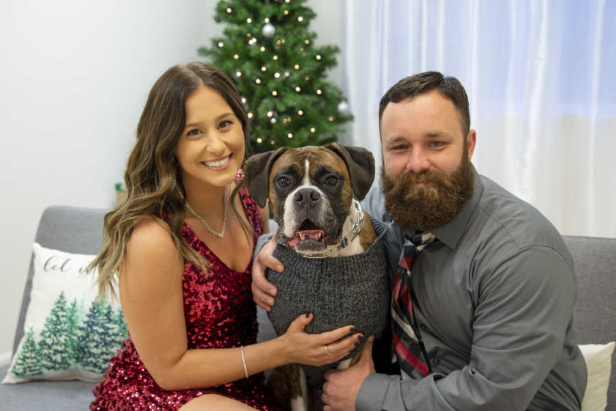Husband and wife in front of Christmas tree with Boxer dog in sweater