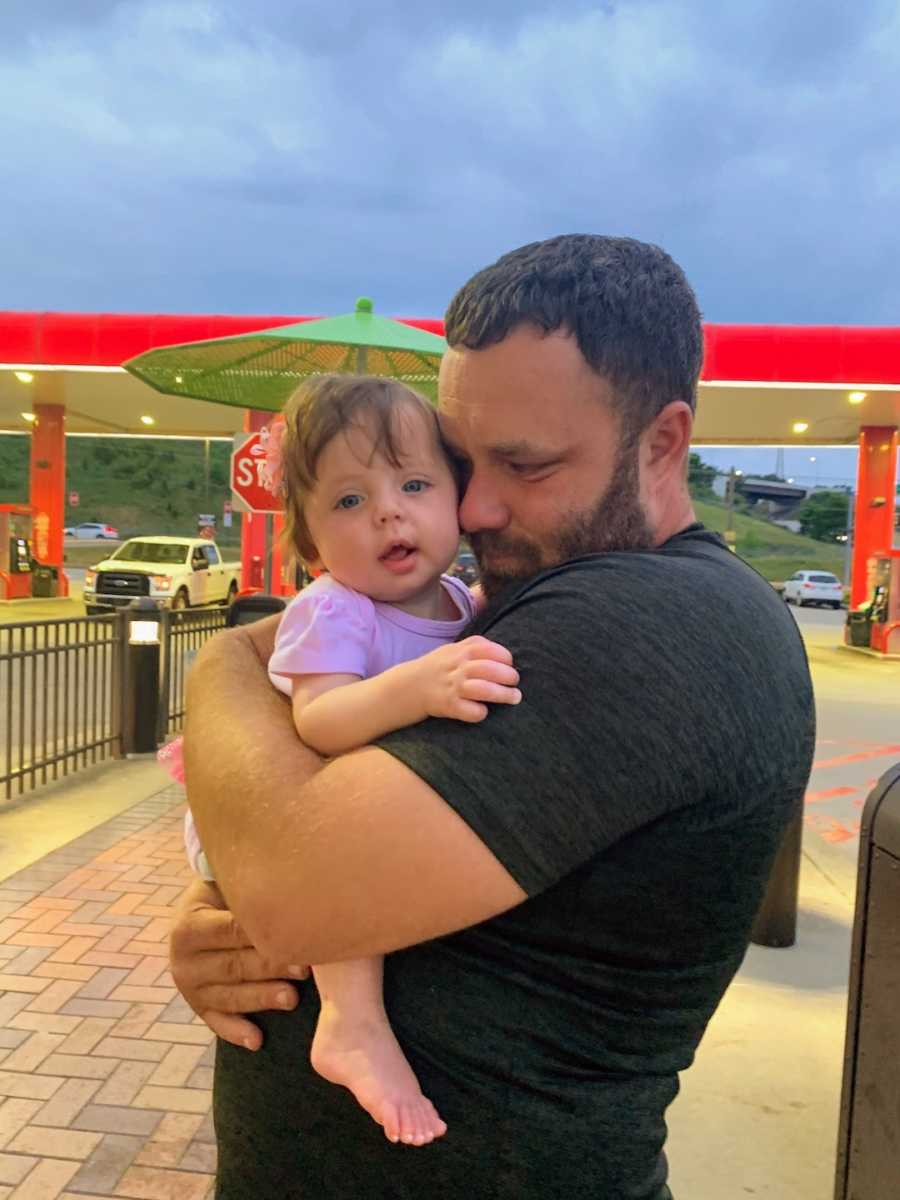 Father holding daughter while crying at a gas station
