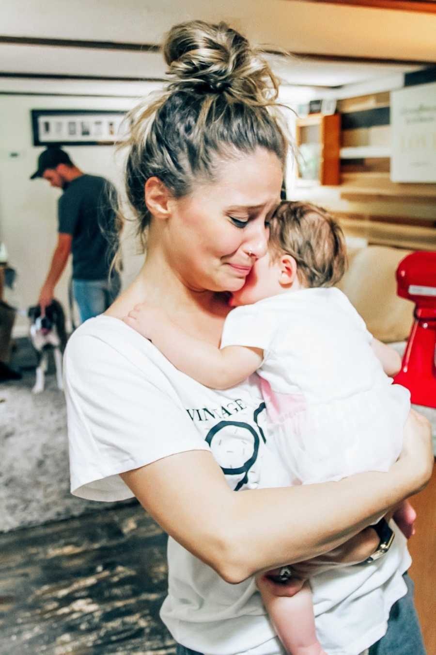 Mom holding adopted daughter and crying