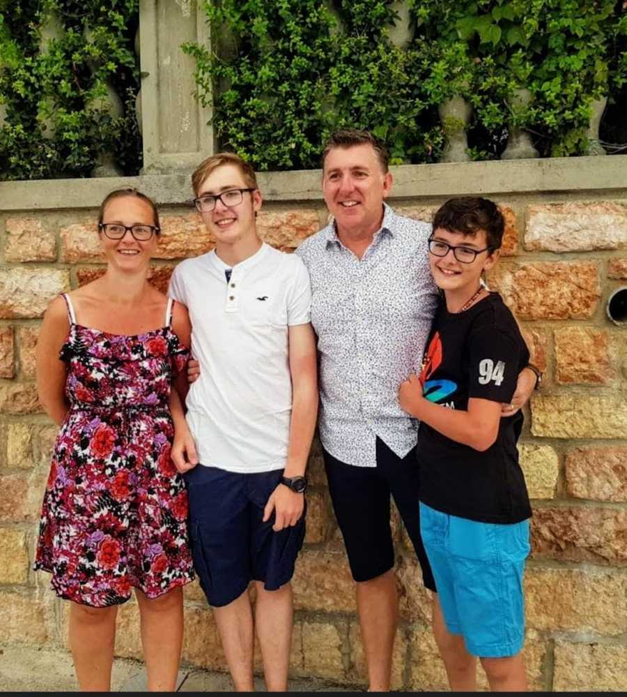 Family of four with arms around each other smiling in front of stone wall