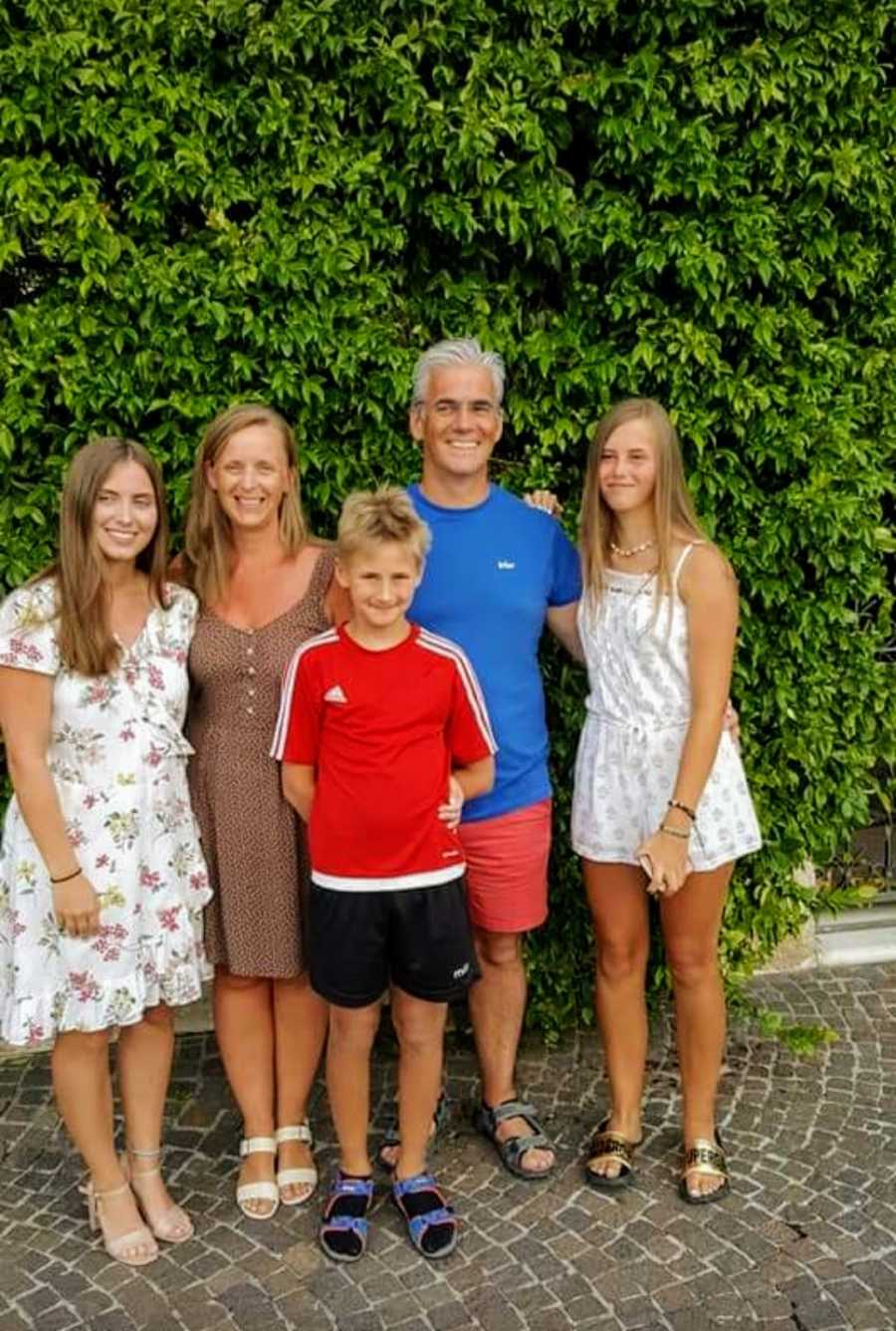 Family of five standing in front of hedge and smiling