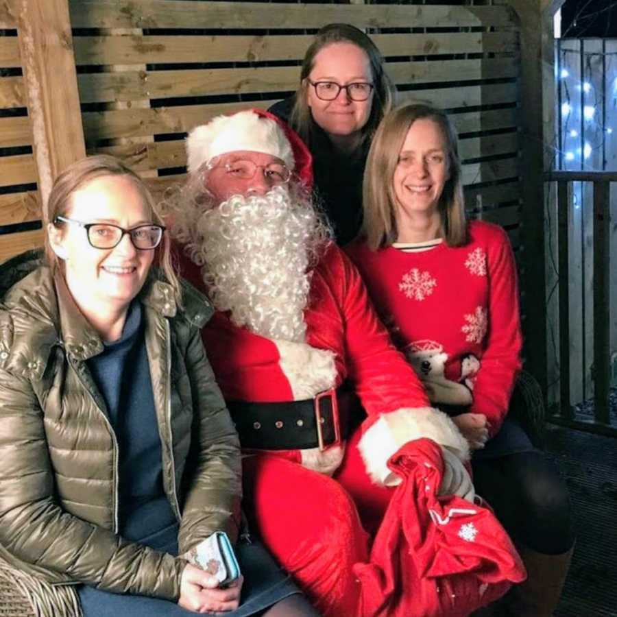 Three sisters sitting on a bench wearing red with Santa Claus