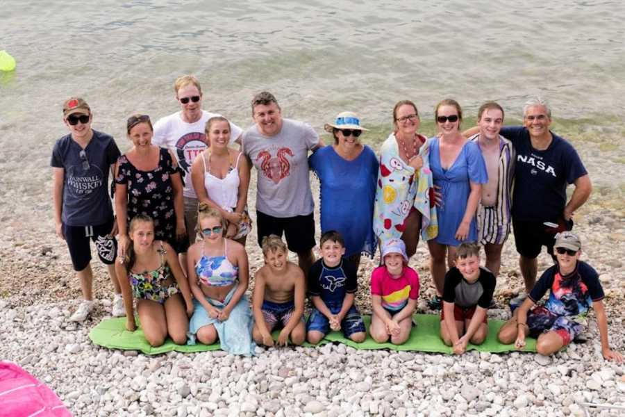 Large family standing on beach in front of water with arms around each other