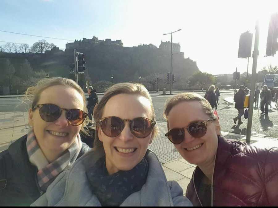 Three sisters wearing sunglasses taking smiling selfie