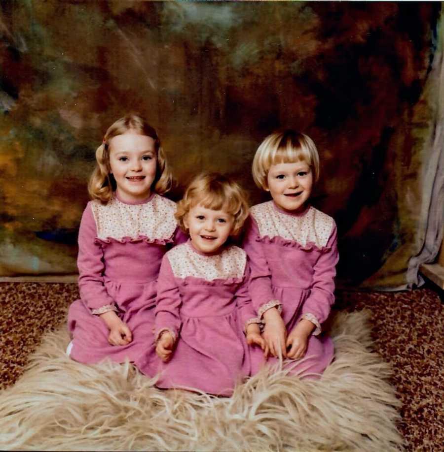 Three blonde sisters wearing pink dresses kneeling on floor