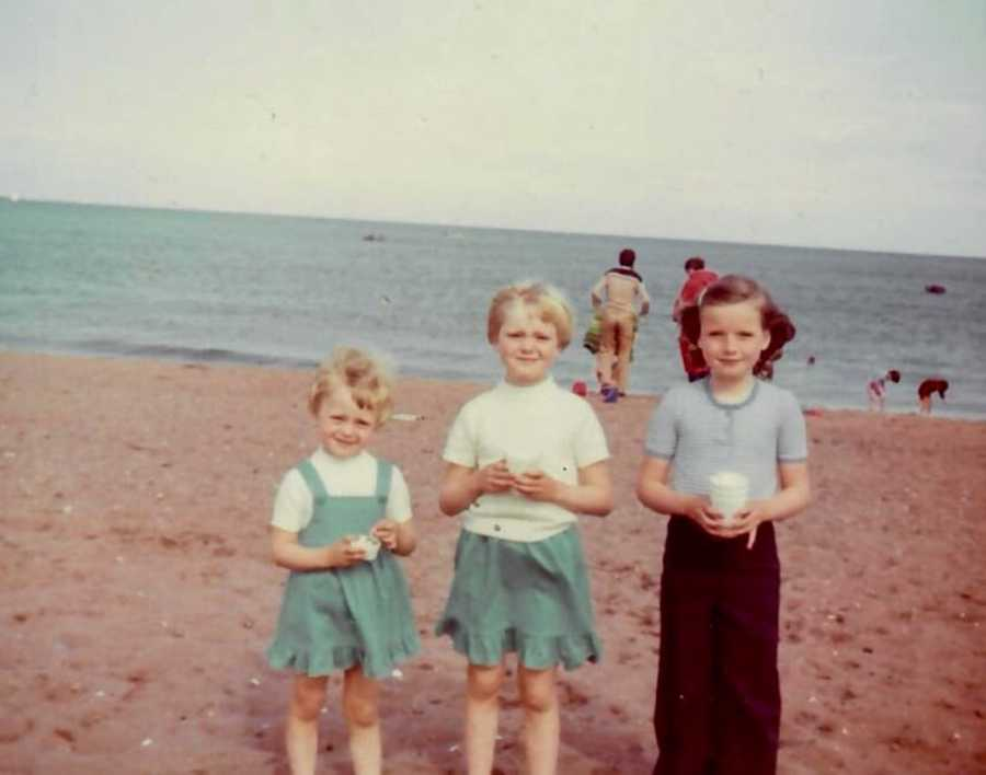 Three sisters standing on beach in front of ocean