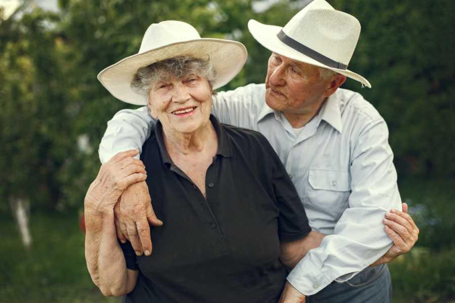Grandparents wearing hats hugging