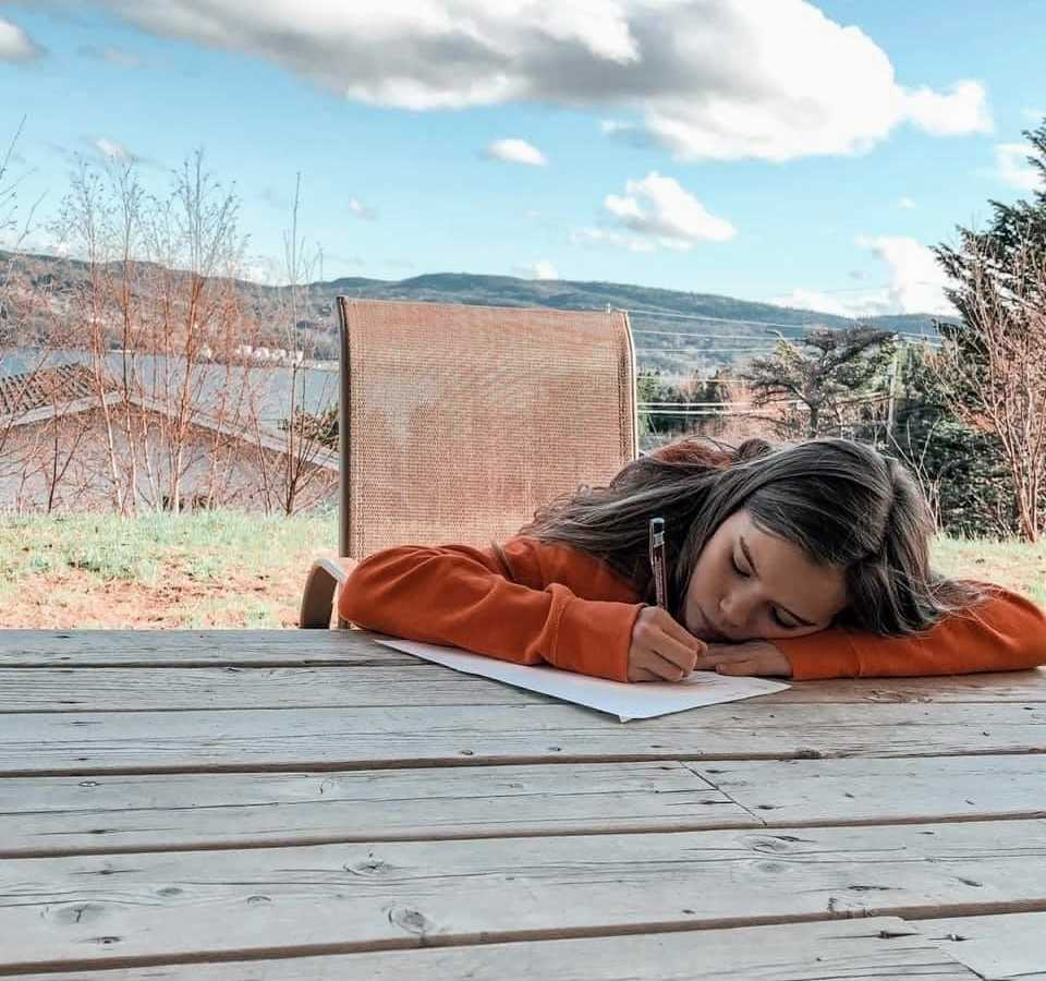 A girl rests her head on an outdoor table while writing