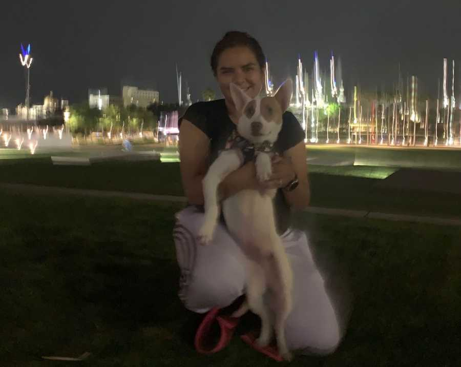 girl holding a dog in front of a city landscape