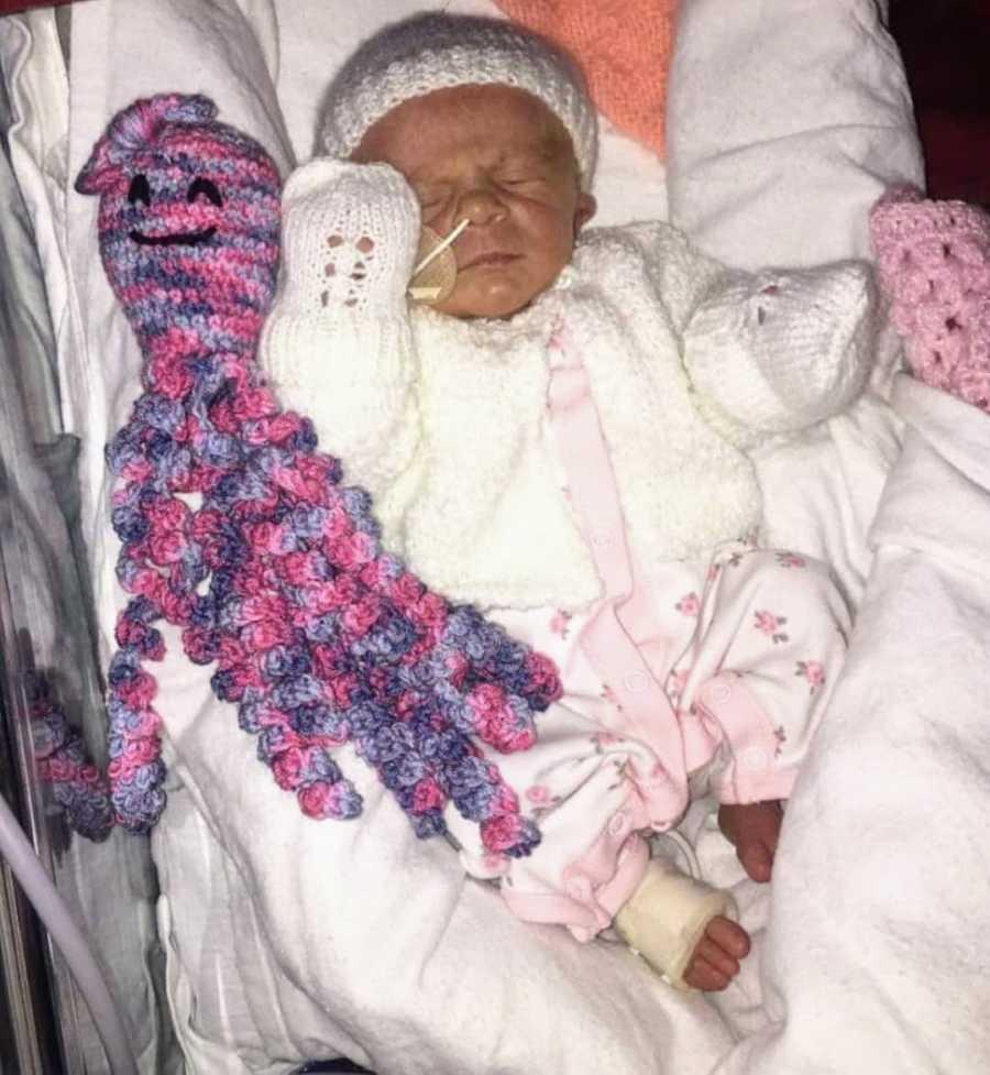 Newborn baby wearing white sleeping in crib