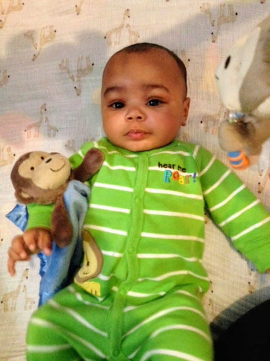 Baby wearing green onesie holding monkey stuffed animal
