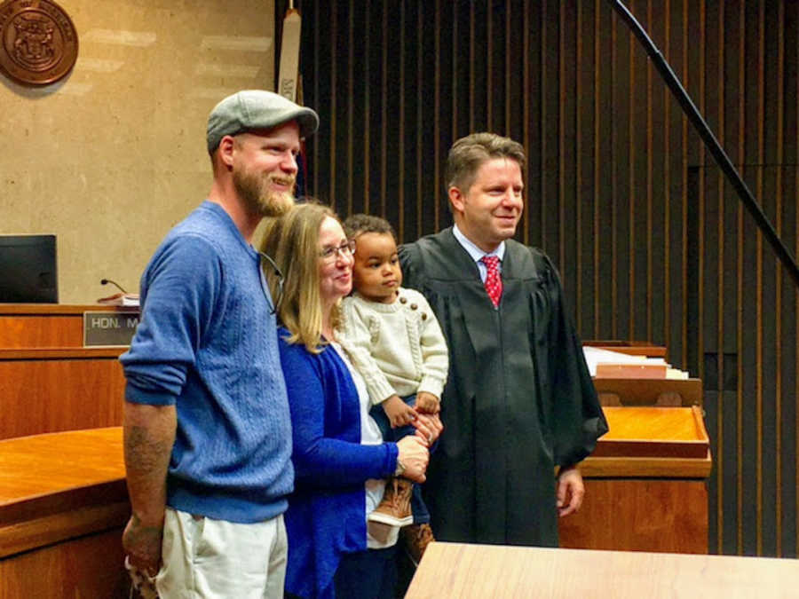 Family standing in adoption court with judge