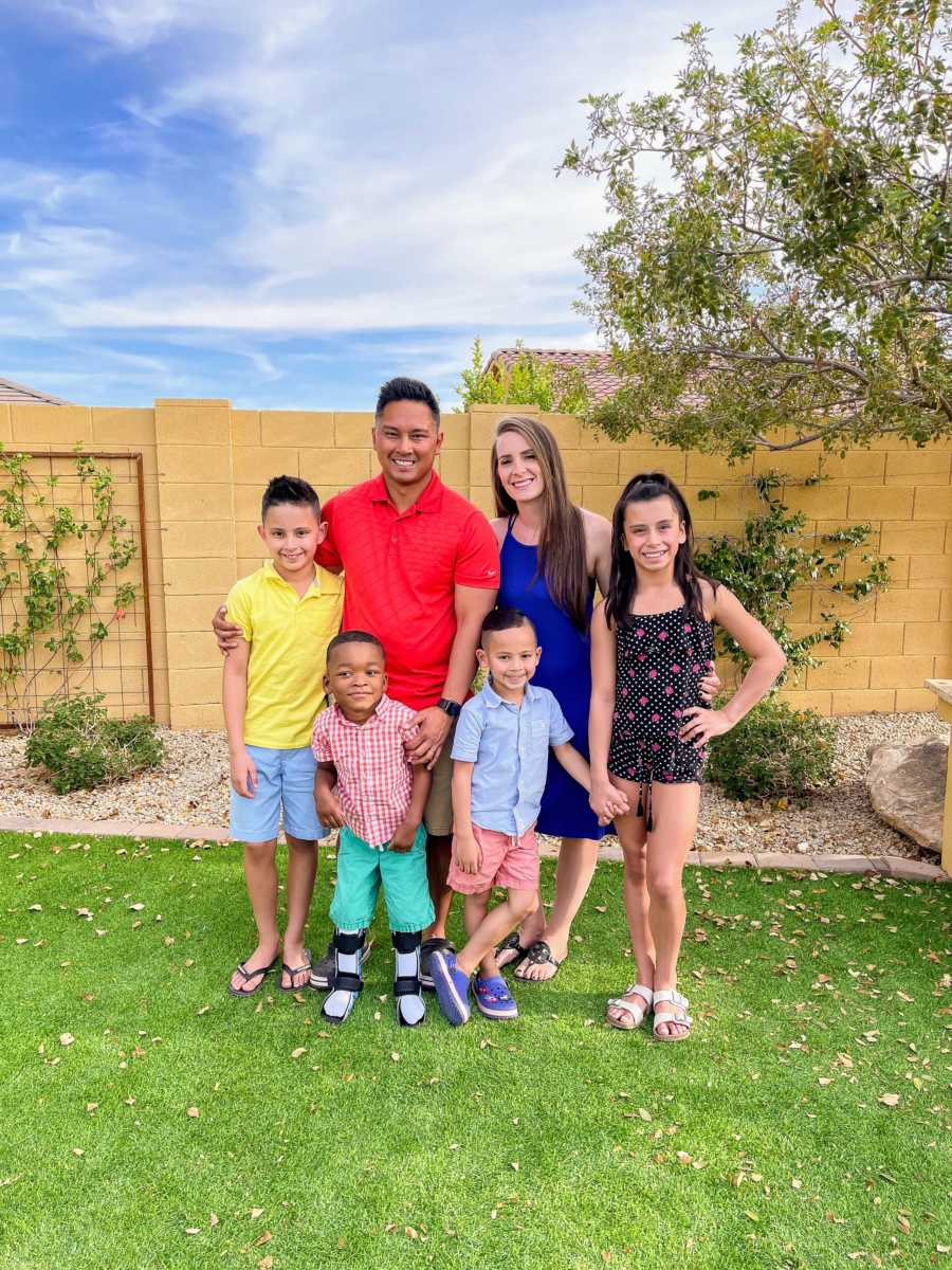 Family of 6 standing in backyard with arms around each other and smiling
