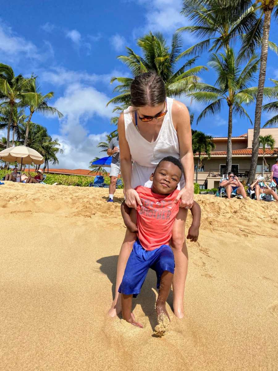 Mom and adoptive son standing together on a beach with palm trees