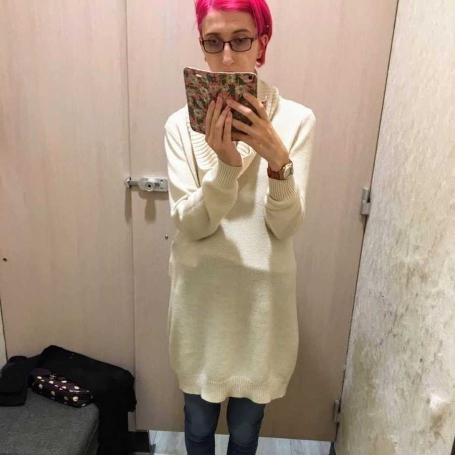 Woman with pink hair taking selfie in a dressing room