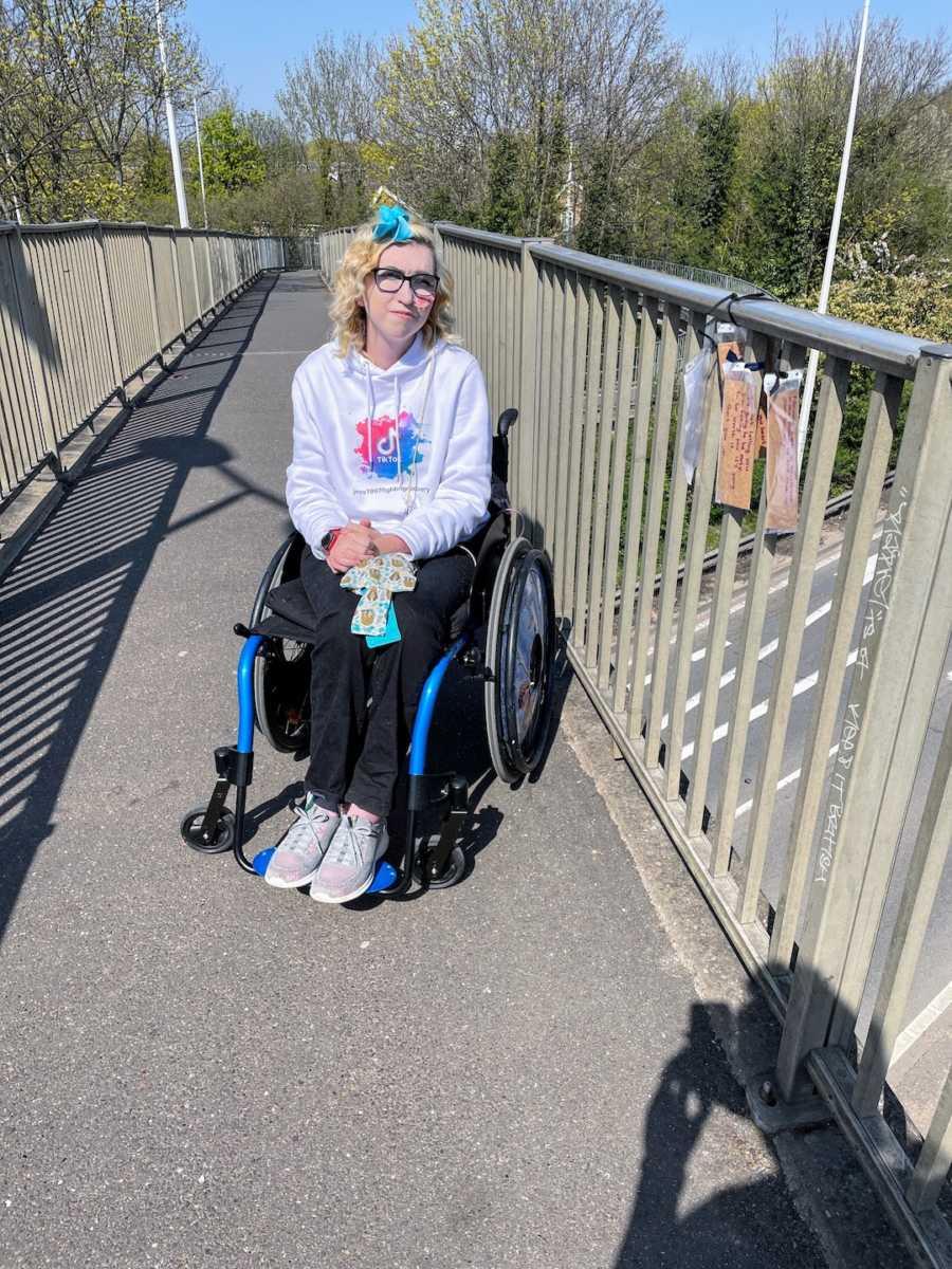 Woman in wheelchair on bridge