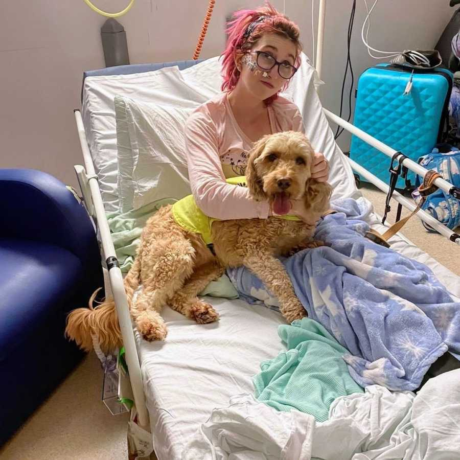 Woman with pink hair holding service dog in inpatient care