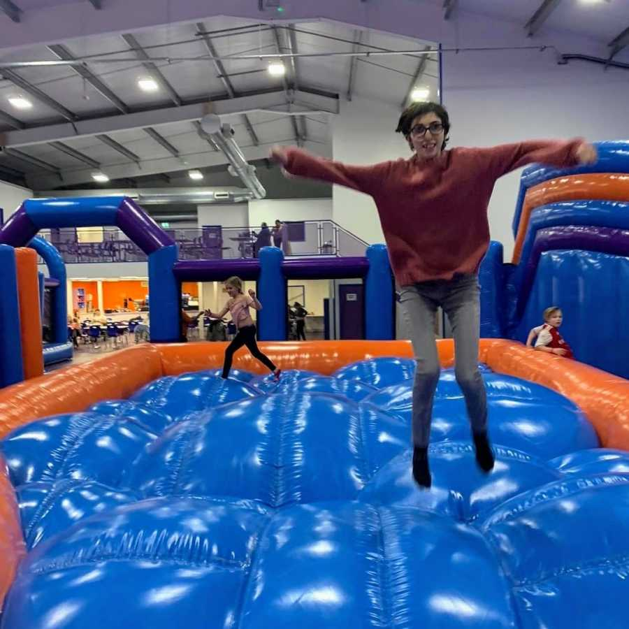 Woman jumping on blue and orange inflatable bouncy castle