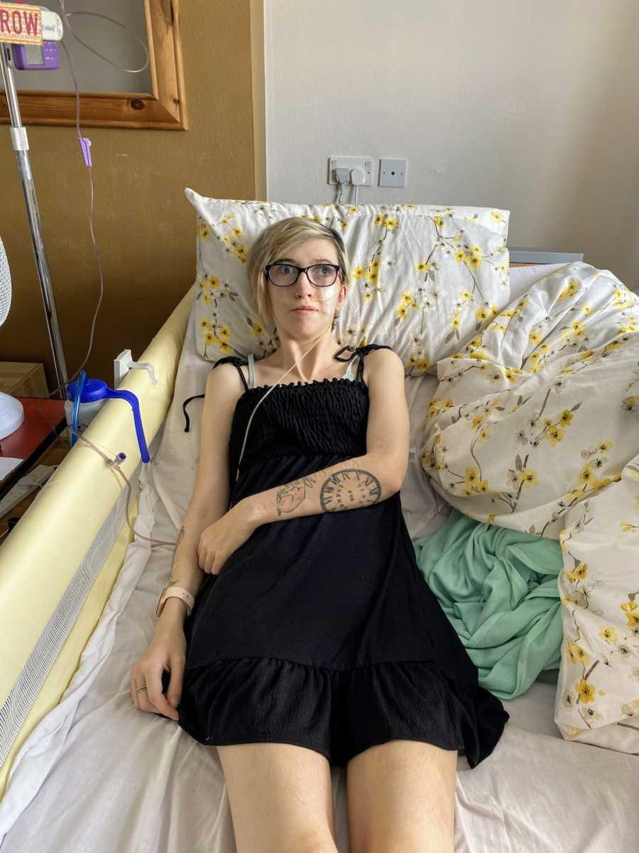 Woman wearing black dress lying in a hospital bed