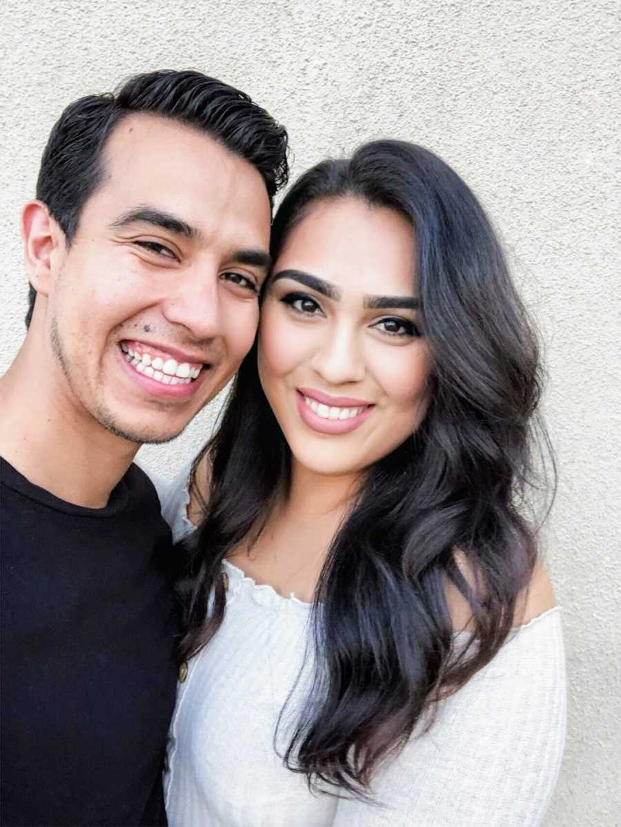 Selfie of a couple smiling in front of white wall