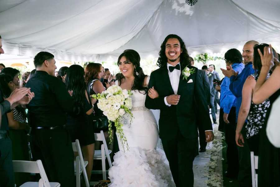 Newlywed couple walking down aisle holding flowers with cheering guests