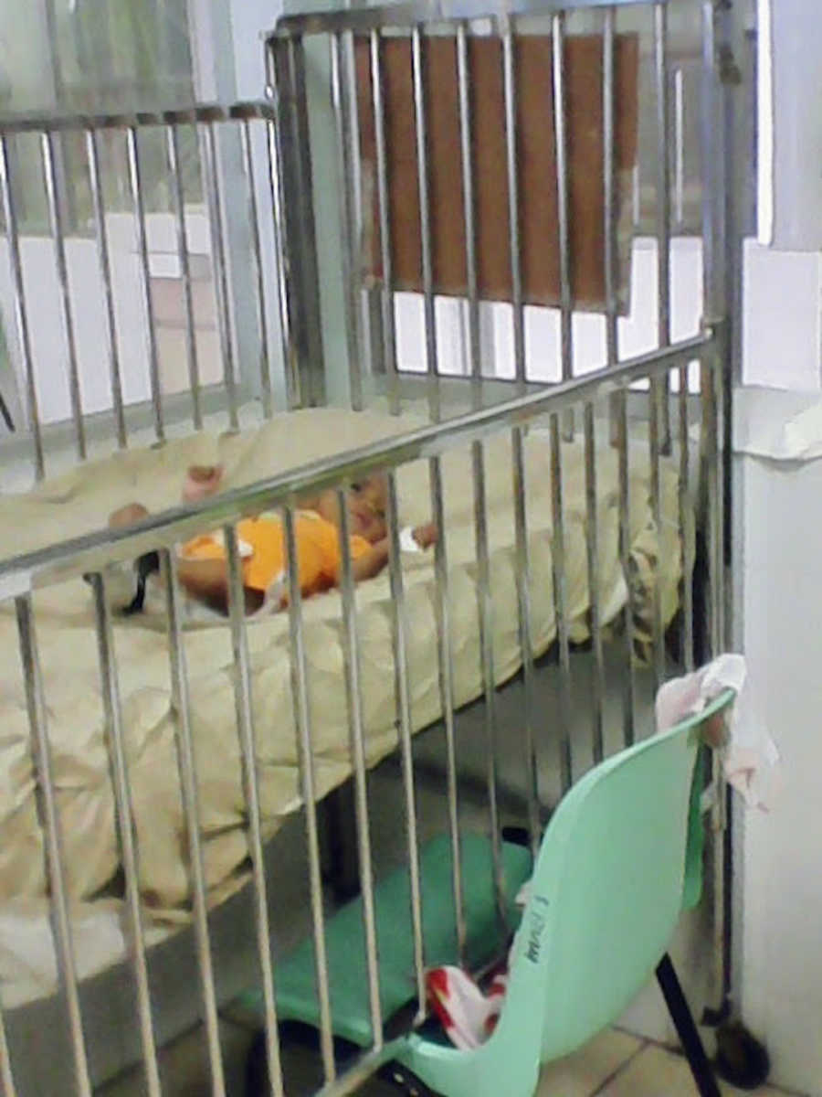 Baby wearing yellow in crib at hospital