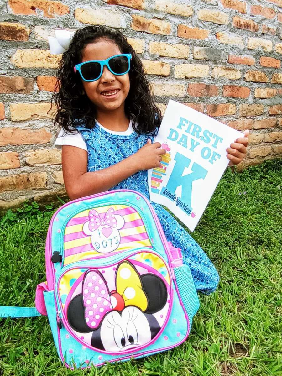 Young girl sitting outside with backpack wearing sunglasses